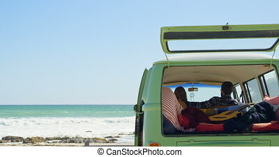 Rear view of couple sitting in a van 4k - Rear view of ...