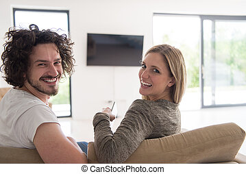 Rear view of couple watching television in living room their...