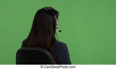 Rear view of customer service representative with headset against green screen