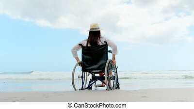 Rear view of disabled woman sitting on wheelchair at beach 4k