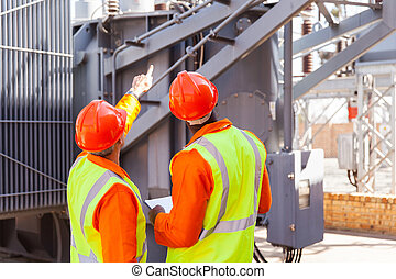 rear view of electrical engineers in substation