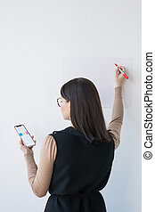 Rear view of elegant businesswoman or coach with smartphone making presentation