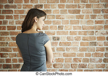 Rear view of elegant woman on the wall