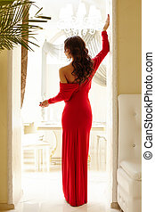 Rear view of elegant woman with glass of wine