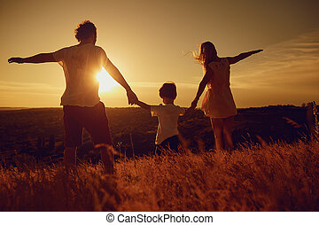Rear view of family standing in nature at sunset