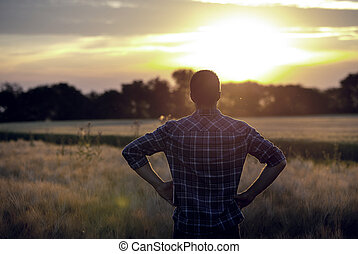 Rear view of farmer in field at sunset