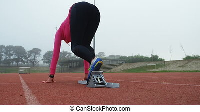 Rear view of female athlete taking starting position and ...