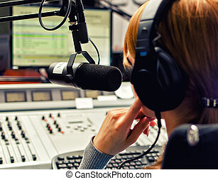 Rear view of female dj working in front of a microphone on ...