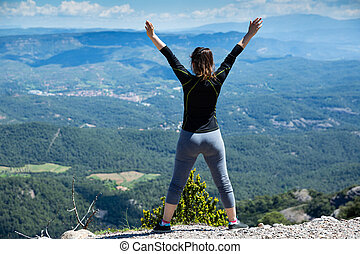 Rear view of female with raised hands on top of mountain