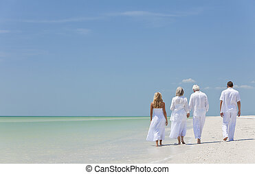 Rear view of four people, two seniors, couples or family generations, holding hands, walking on a tropical beach