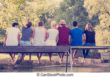 rear view of friends enjoying watermelon while sitting on the wooden bridge