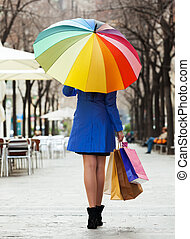 girl in cloak with shopping bags and umbrella