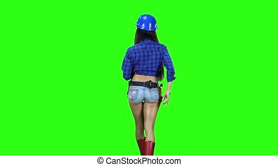Rear view of girl in hat and shorts with a hammer on the belt going on green background