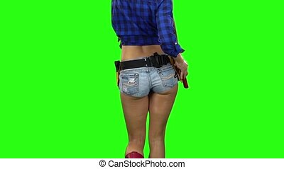 Rear view of girl in shorts with a hammer on the belt going on green background. Slow motion. Close up