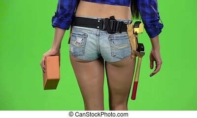 Rear view of girl in shorts with brick in hand walking on a...