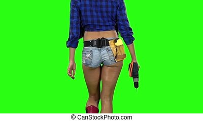 Rear view of girl in shorts with drill in hand walking on...