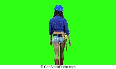 Rear view of girl wearing helmet and shorts walking on green...