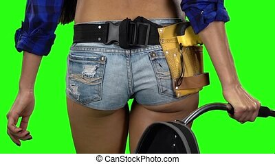 Rear view of girls walking in shorts on a green background....
