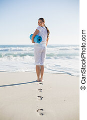 Rear view of gorgeous woman on the beach holding exercise mat looking over shoulder at camera