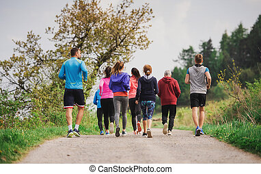 Rear view of group of multi generation people running a race competition in nature.
