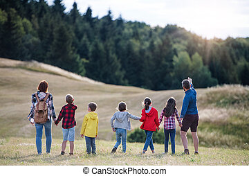 Rear view of group of school children with teacher on field trip in nature.