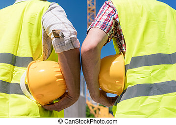 Rear view of hands of workers holding yellow hard hats of contruction workers