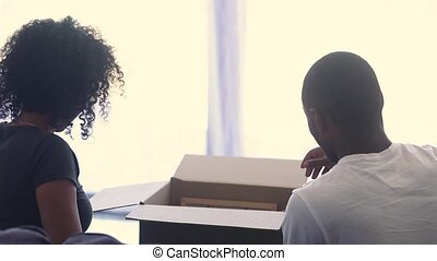 Rear view of happy african american couple unpacking boxes together