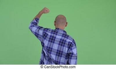 Rear view of happy bald hipster man with fists raised -...