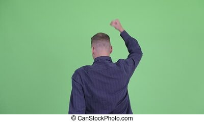 Rear view of happy businessman with fists raised - Studio...