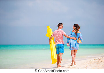Rear view of happy couple in honeymoon on the beach