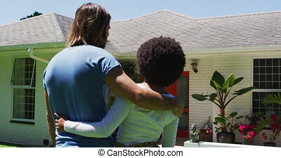 Rear view of happy mixed race couple looking at their new house