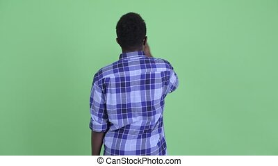 Rear view of happy young African hipster man looking around