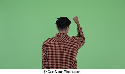 Rear view of happy young African man with fists raised
