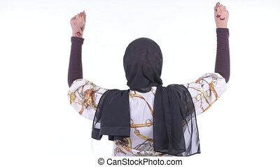 Rear view of happy young African Muslim woman with fists...
