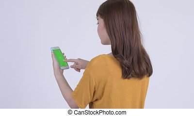 Rear view of happy young Asian woman using phone