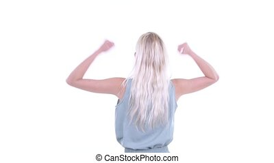 Rear view of happy young blonde woman with fists raised -...
