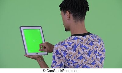 Rear view of happy young handsome African man using digital tablet