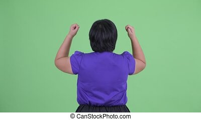 Rear view of happy young overweight Asian woman with fists...
