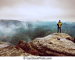 Rear view of hiker in yellow black jacket on mountain while enjoying daybreak