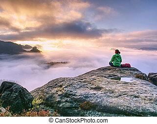 rear view of hiker woman on top of mountain peak in rocks