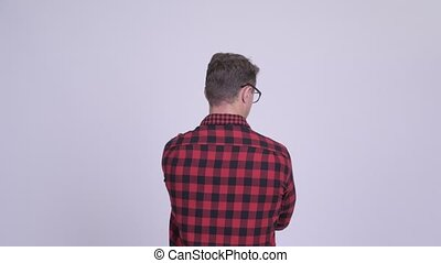 Rear view of hipster man pointing finger against white...