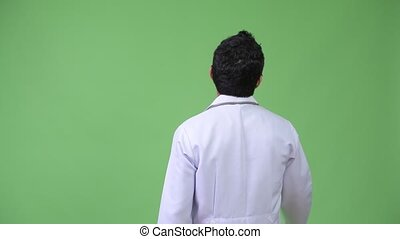 Rear view of Hispanic man doctor pointing finger - Studio...