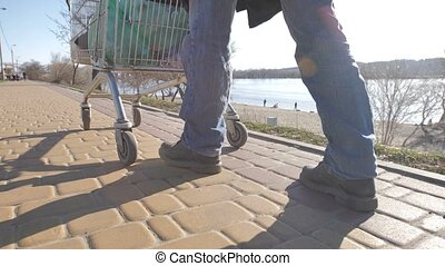 Rear view of homeless man's legs walking with cart - Rear...