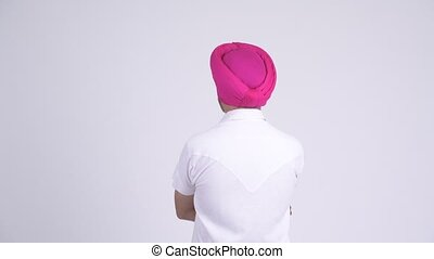 Rear view of Indian Sikh man with turban pointing finger -...