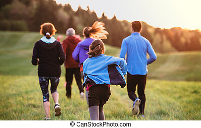 Rear view of large group of people cross country running in nature.