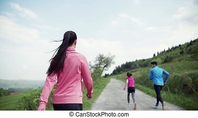 Rear view of large group of people cross country running in...