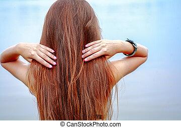 Rear view of long haired brunette posing against sea water on seaside