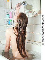 long-haired girl in bath - Rear view of long-haired girl in ...