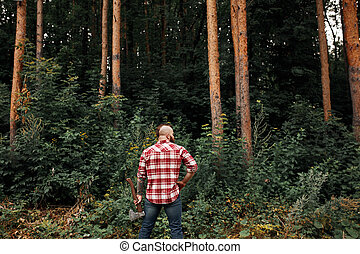 Rear view of lumberjack in forest holding an axe on his shoulder