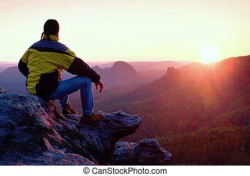 Rear view of male hiker in yellow black jacket sitting on rocky cliff while enjoying daybreak above valley